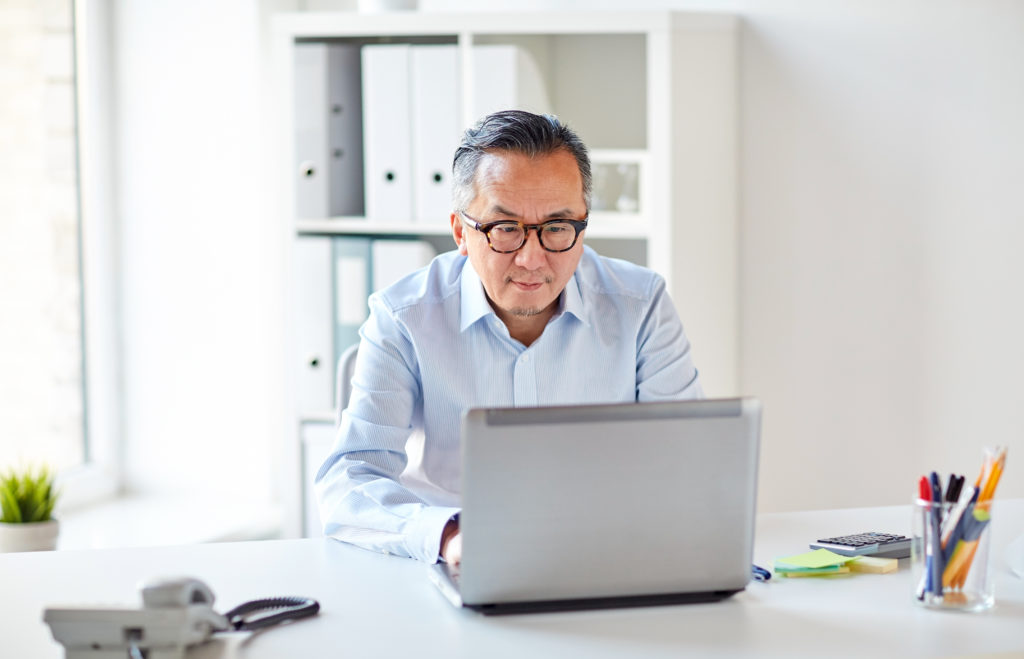 Man on laptop accessing Online Therapy